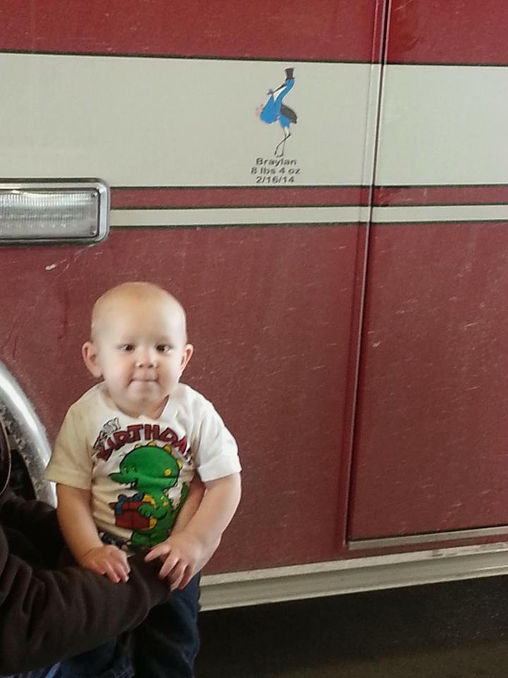 Braylan age 1 next to the ambulance where he was delivered 1 year ago