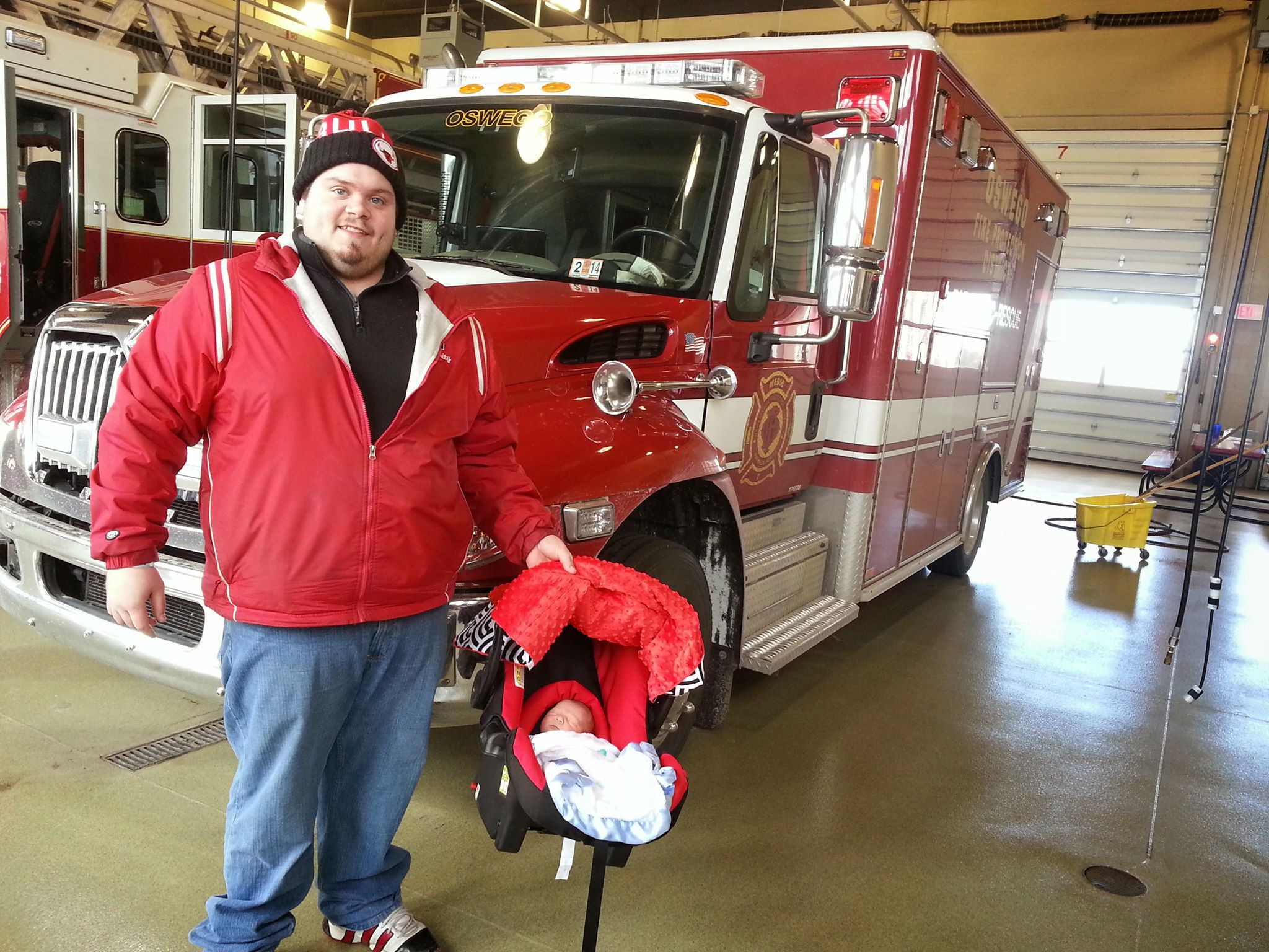 Proud Dad, Jeff, holds newborn son, Braylan, in front of the ambulance where he was delivered